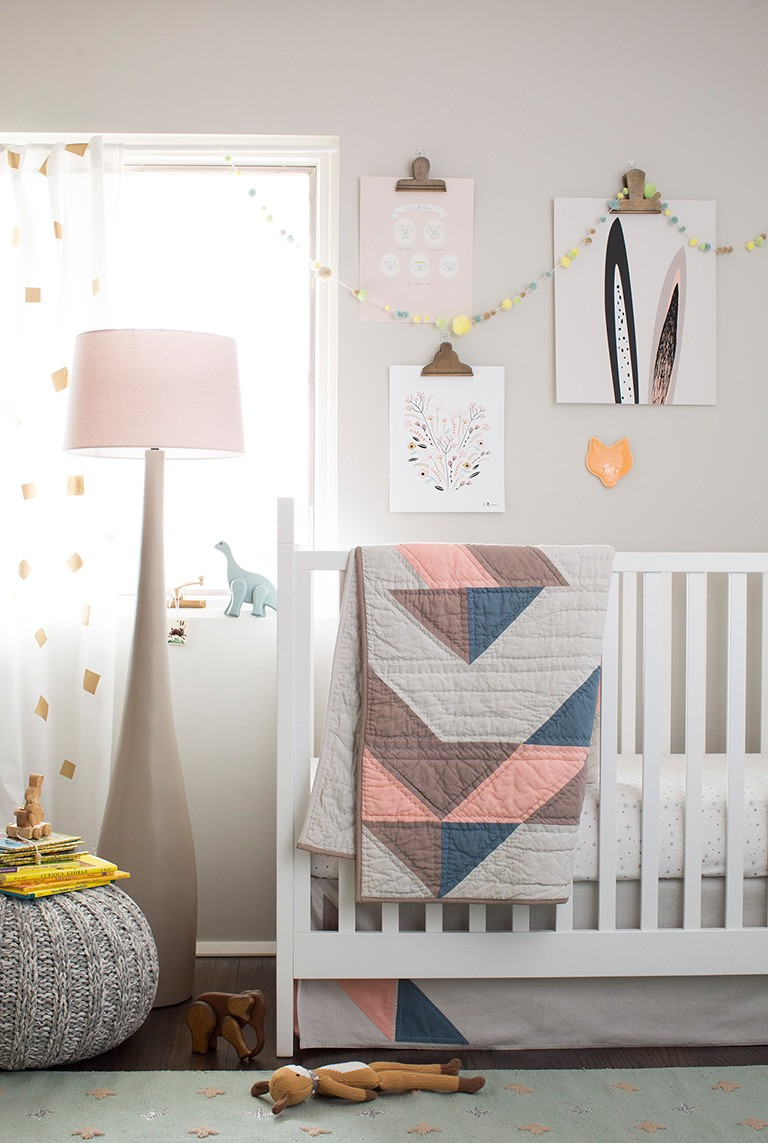 Neutral nursery with a white crib, pink floor lamp, sheer patterned curtains, and a muted green rug
