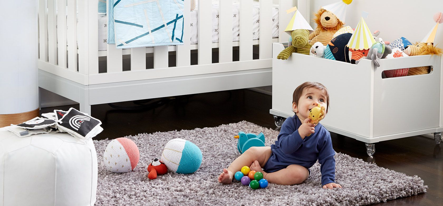 Baby playing with toys on the floor of a nursery