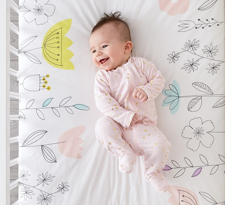 Smiling baby, laying in a crib.