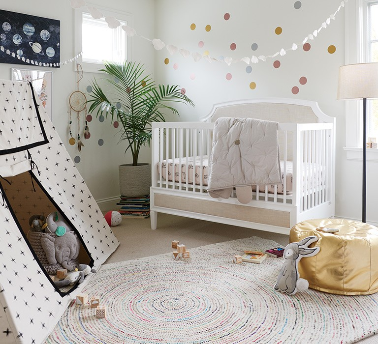Gender neutral nursery, with crib, play tent, pouf, and rug.