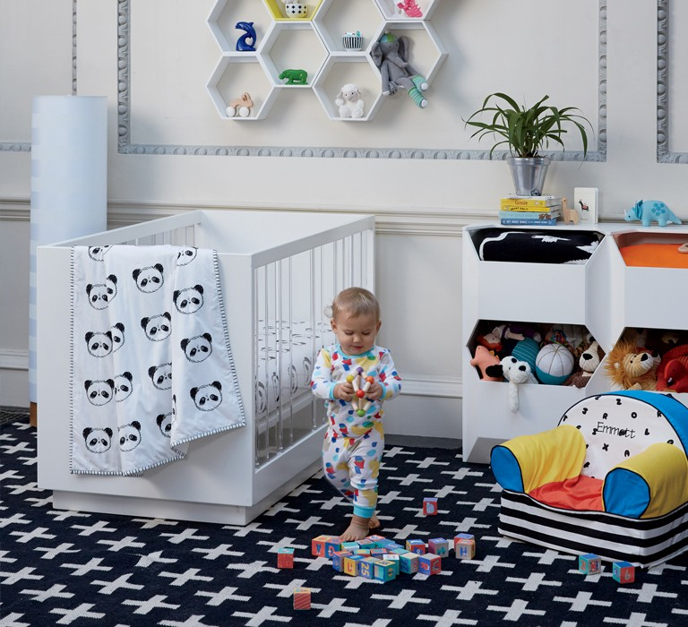 child playing with wooden toy in his nursery