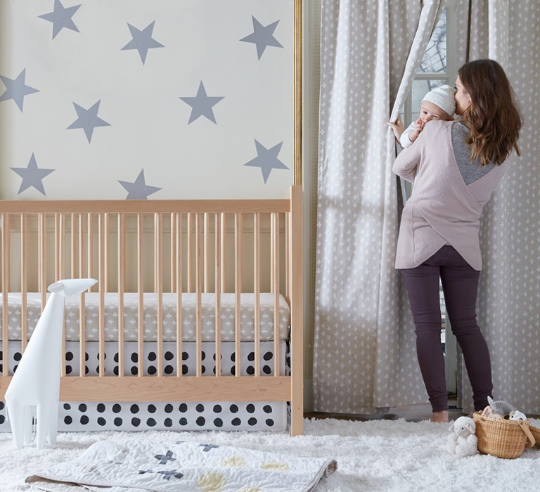 Mother holding her baby in a gender neutral nursery.