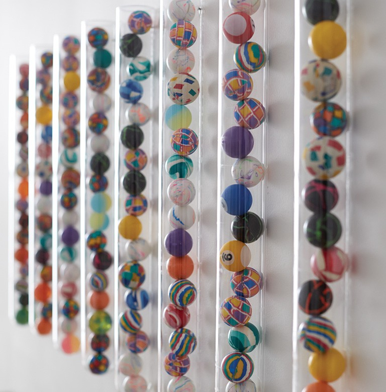 decorate your kids bedroom bouncy balls in narrow plastic tubes affixed to a wall